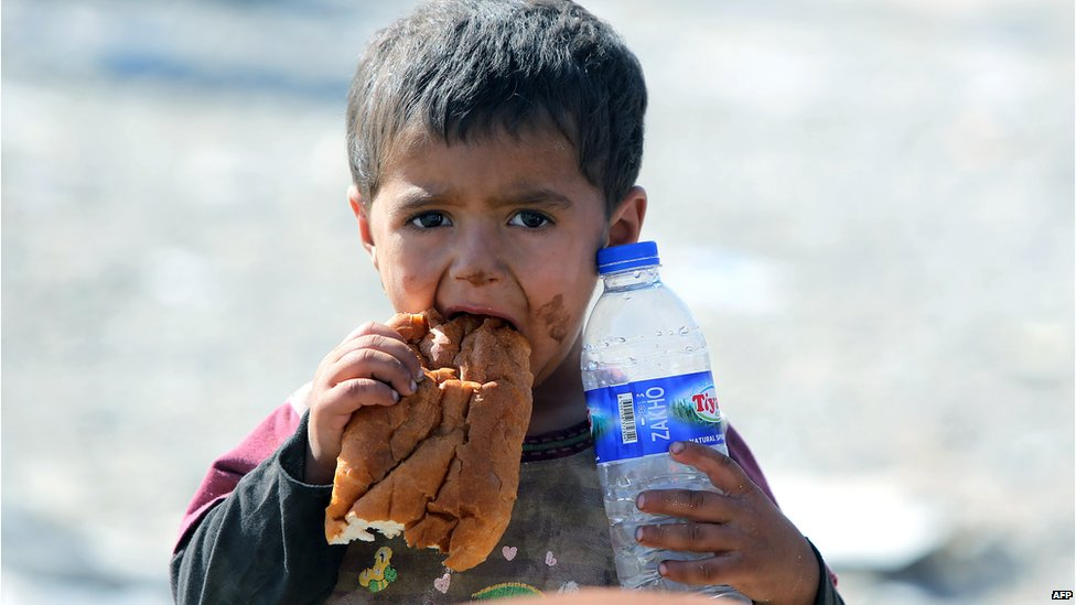 A displaced Iraqi boy from the Yazidi community eats a piece of bread and holds a bottle of water as they cross the Iraqi-Syrian border at the Fishkhabur crossing, in northern Iraq, on 11 August 2014.