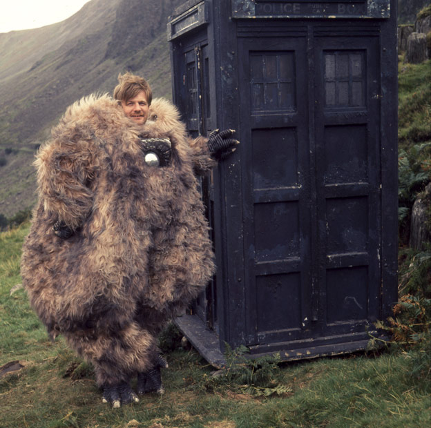 Reg Whitehead standing beside the Tardis wearing a Yeti costume during filming