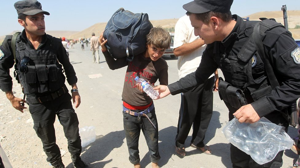 Peshmerga forces hand out water bottles to displaced Iraqi families from the Yazidi community as they cross the Iraqi-Syrian border at the Fishkhabur crossing, in northern Iraq, on 11 August 2014.
