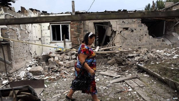 Woman walks past damaged house in Donetsk (11 August 2014)