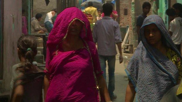 Indian women walking down a street