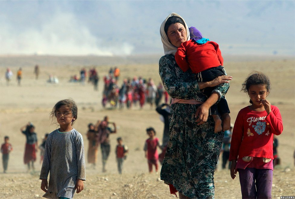 Displaced people from the minority Yazidi sect walk towards the Syrian border, on the outskirts of Sinjar mountain