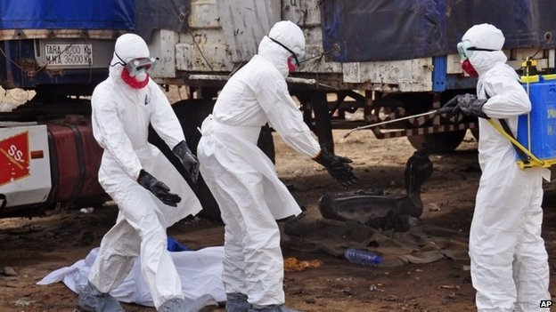 The body of a man suspected of dying from the Ebola virus lies on the ground, as health workers, right, spray themselves with disinfectant, in the capital city of Monrovia, Liberia (12 August 2014)