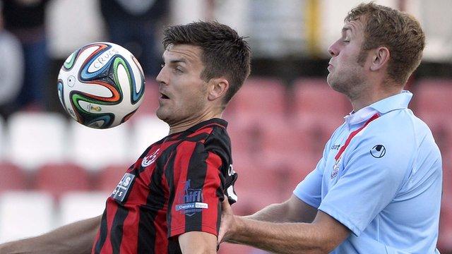 Crusaders forward Dairmuid O'Carroll shields the ball from Ballymena's Johnny Taylor