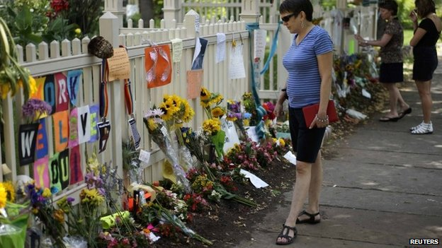 "A woman looks at an impromptu memorial to actor Robin Williams outside the house used in his breakout hit TV show ""Mork and Mindy"" in Boulder, Colorado 13 August 2014"