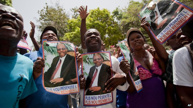 Supporters of Haiti's former President Jean-Bertrand Aristide hold up images of him in front of his home in Port-au-Prince, August 14, 2014