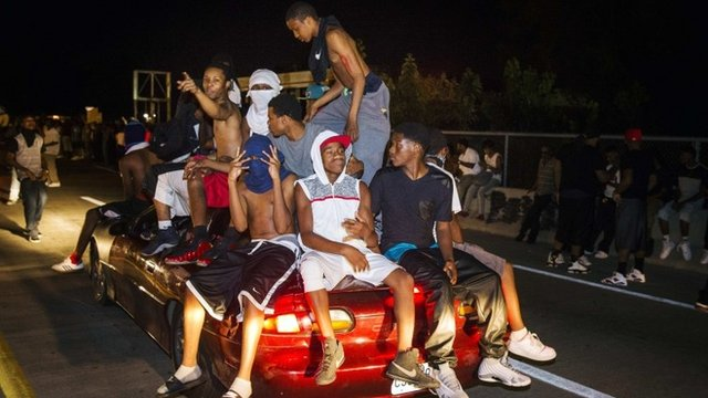 Protesters chant as they ride on a car during a peaceful demonstration as communities continue to react to the shooting of Michael Brown in Ferguson, Missouri August 14, 2014