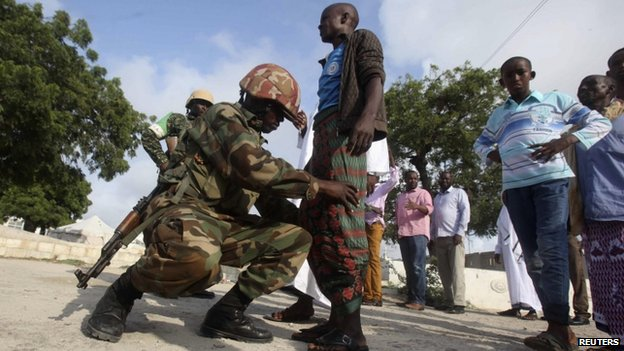 A soldier serving in the African Union Mission in Somalia frisks Muslims before allowing entry to attend Eid al-Fitr prayers to mark the end of the fasting month of Ramadan at a mosque in Somalia's capital Mogadishu, 28 July 2014