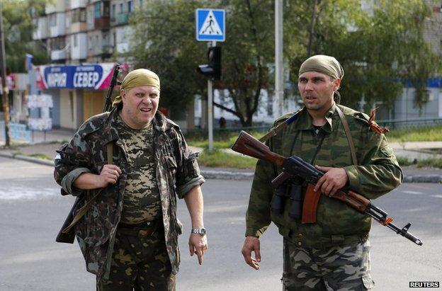 Rebels patrolling a street in Makiika, near Donetsk, 19 August