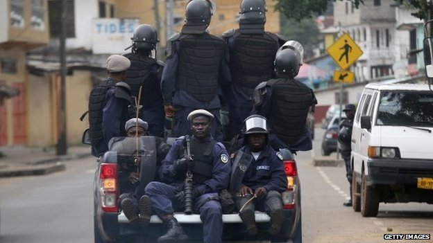 Members of Liberia's Ebola Task Force ride in the back of a pickup as they enforce a quarantine on the West Point slum on 20 August 2014 in Monrovia, Liberia