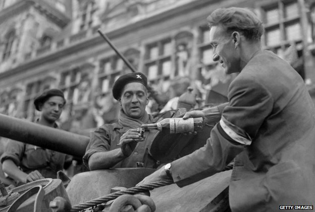 Parisian gives a French soldier a glass of cognac (25 August 1944)