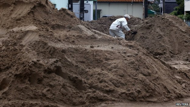 local resident removes mud in the rain at a site where a landslide swept through a residential area at Asaminami ward in Hiroshima, western Japan, August 22, 2014.