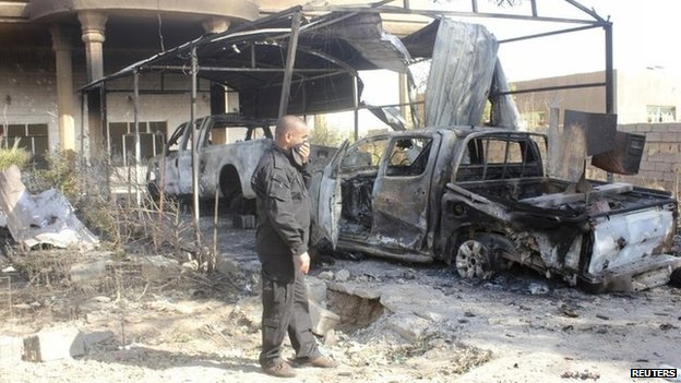 An Iraqi security officer stands next to the wreckage of a vehicle belonging to the Islamic State in Diyala province, 12 August 2014