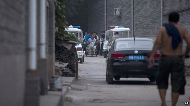 Chinese policemen and men claiming to be villagers block an alleyway leading to the venue for the Beijing Independent Film Festival on 23 August 2014