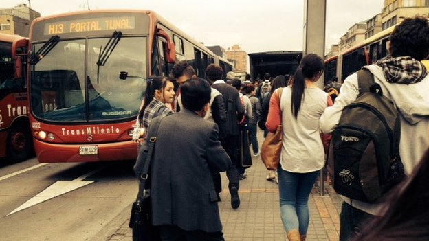 Passengers wait for a Transmilenio bus in Bogota