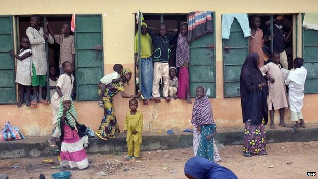 "A picture taken on August 21, 2014 shows Internally Displaced People (IDP) standing outside a classroom they found shelter in, at Gulak camp in Nigeria""s northeastern Adamawa State."