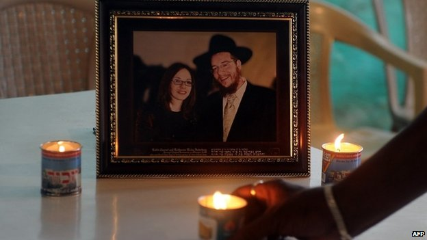 A member of staff places a traditional Jewish Memorial candle in front of a photograph of slain Rabbi Gavriel Holtzberg and his wife Rivkah,at the Jewish cultural centre in Mumbai, November 2012