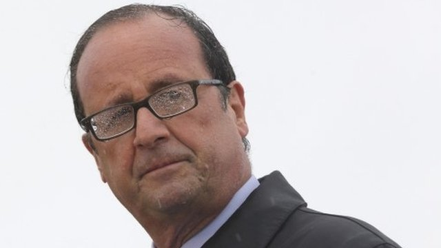 French President Francois Hollande delivers a speech in the rain on the Ile de Sein, an island located near the Pointe-du-Raz, off the Brittany coast, August 25, 2014