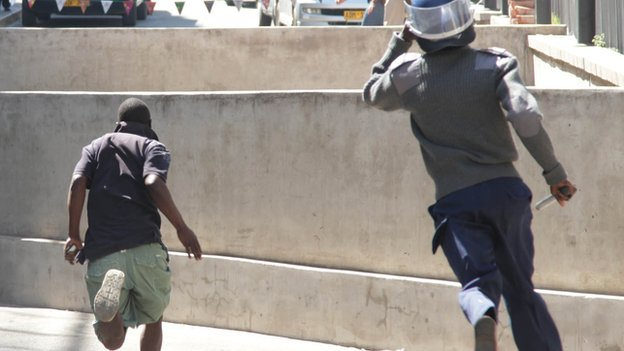 A riot policeman chasing an MDC protester in Harare, Zimbabwe - Wednesday 27 August 2014