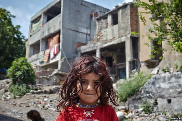 Aysha, 5, stands outside an abandoned building in Istanbul that has been her home for half a year