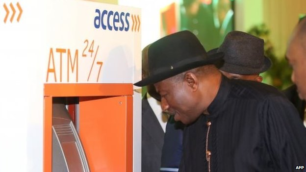 Nigerian President Goodluck Jonathan tries to make cash withdrawal with his electronic identity card during the launching of the cards in Abuja on 28 August 2014
