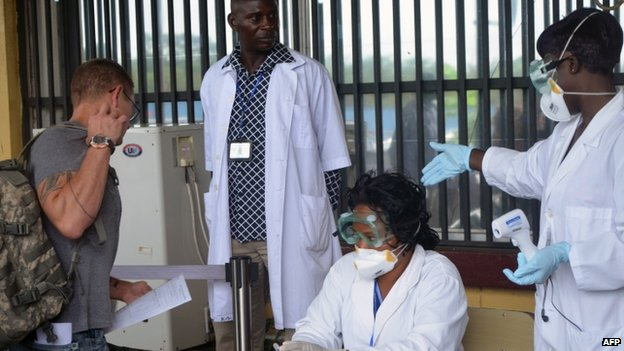 Health agents check a passenger leaving Liberia at the Roberts International Airport near Monrovia (27 August 2014)