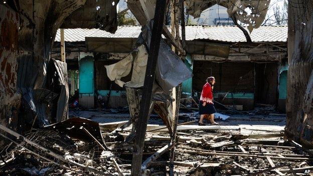 Woman walks past damaged buildings in Donetsk (30 August 2014)