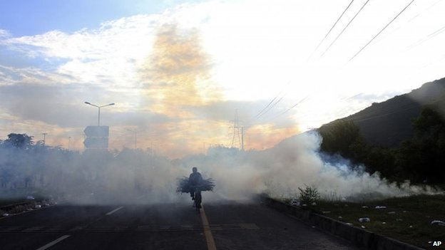 A bicyclist makes his way through tear gas fired by police to disperse protesters