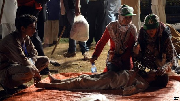 Pakistani supporters of Canadian cleric Tahir ul Qadri give medical treatment to a tear gas victim