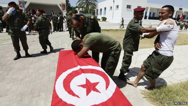 A wounded Tunisian soldier mourns the death of his colleague during his funeral