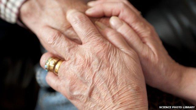 Carer holding an elderly patient's hand