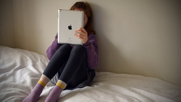 File photo: A young girl browsing the internet in her bedroom, 4 May 2013