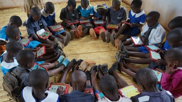 Children in Malawi sit in circle playing app