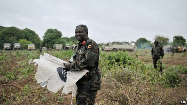 African Union Brigade General Dick Olum with an al-Shebab flag after its forces took the town of Buulomareer, 31 Aug