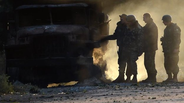 Ukrainian army soldiers check results of overnight shelling in Mariupol, 7 Sept