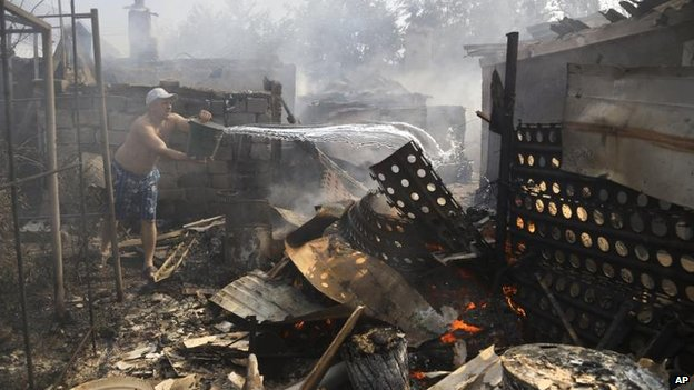 Man puts out fire after shelling in Donetsk, 7 Sept