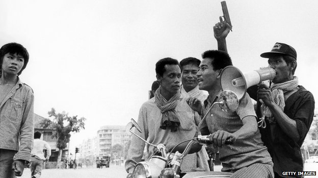 A Khmer Rouge guerrilla soldier holding a gun rides a motorcycle while he and his fellow comrade enter Phnom Penh on 17 April 1975