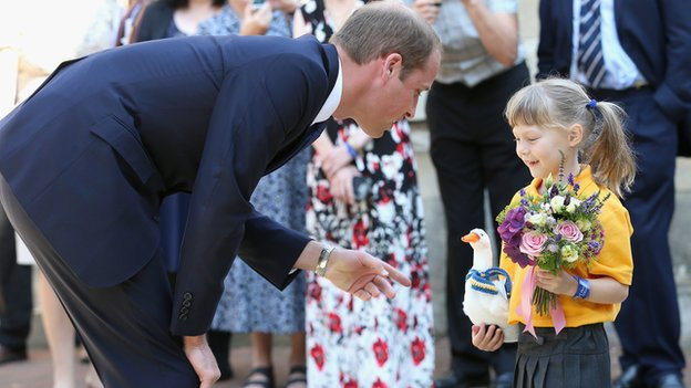 Prince William receives flowers from a young girl
