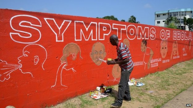 A street artist, Stephen Doe, paints an educational mural to inform people about the symptoms of the deadly Ebola virus in the Liberian capital Monrovia, 8 September 2014