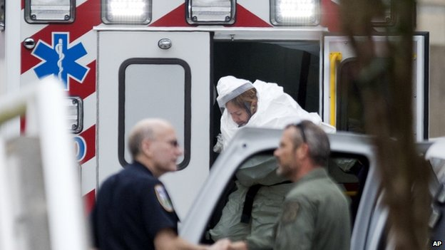 A person wearing a haz-mat suit steps out of an ambulance as an Ebola patient arrives for treatment in Atlanta (9 September 2014)