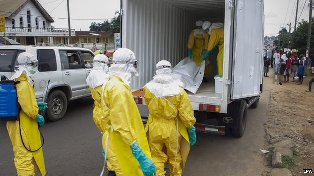 Liberian health care workers on an Ebola burial team collect the body of an Ebola victim in Paynesville on the outskirts of Monrovia, Liberia on 9 September 2014.