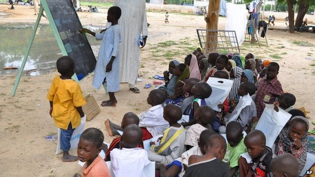 Children who fled their homes following an attacked by Islamist militants in Bama, take a lesson at a camp in Maiduguri, Nigeria, 9 September 2014