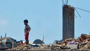 A child on the roof of a ruined building