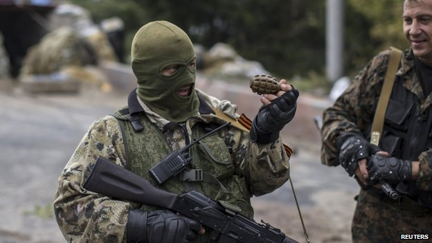 A Pro-Russian rebel holds a hand grenade at a checkpoint near the airport in Donetsk