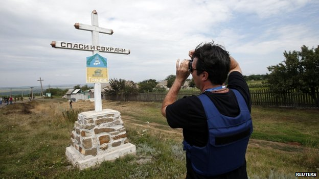 An Organisation for Security and Cooperation in Europe (OSCE) monitor photographs the village sign at the crash site of Malaysia Airlines Flight MH17, near the settlement of Grabovo in the Donetsk region