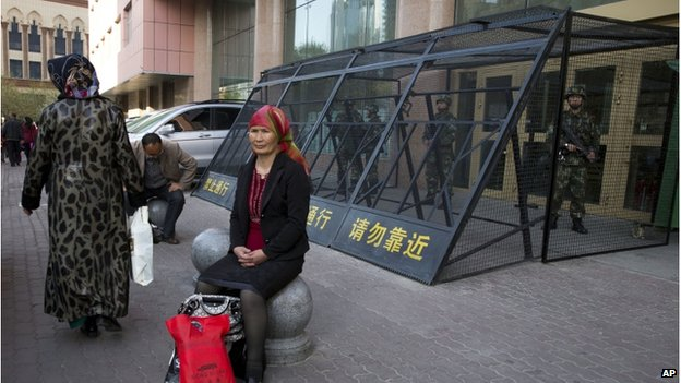 In this 1 May 2014 file photo, a Uighur woman rests near a cage protecting heavily armed Chinese paramilitary policemen on duty in Urumqi in China's northwestern region of Xinjiang