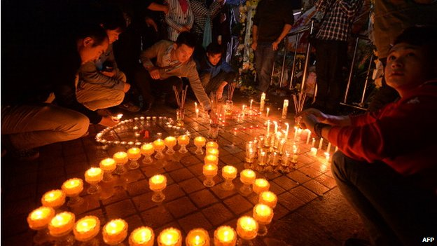 Chinese mourners light candles at the scene of the terror attack at the main train station in Kunming, Yunnan Province on 2 March 2014