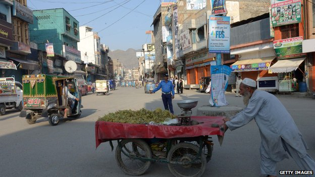 A Pakistani man pushes his fruit cart at a market in Mingora on 11 October 2013, the hometown of education activist Malala Yousafzai.