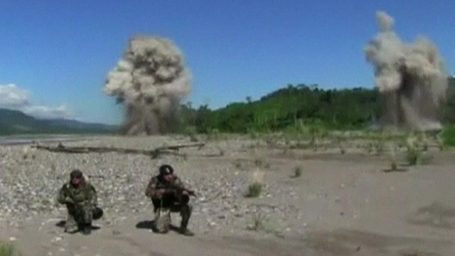 soldiers guard explosions on airstrip