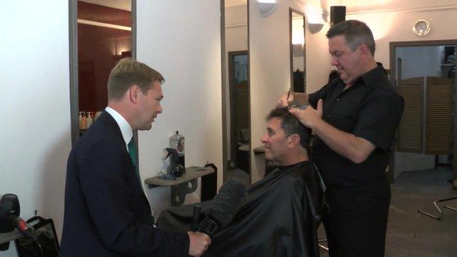 Christian Fraser speaking to hairdresser and customer